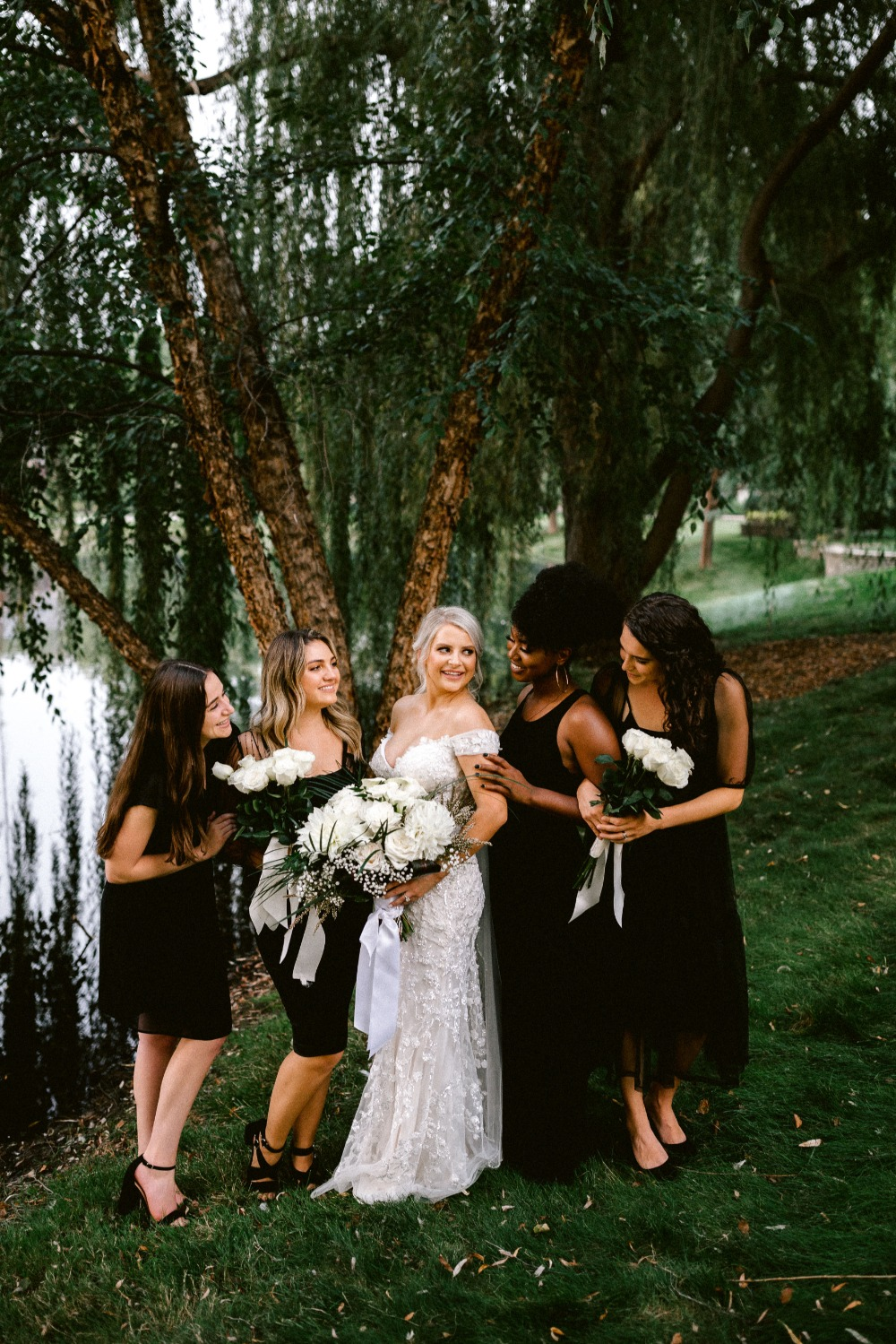 bridesmaids in mismatched black dresses paired with wedding bouquets