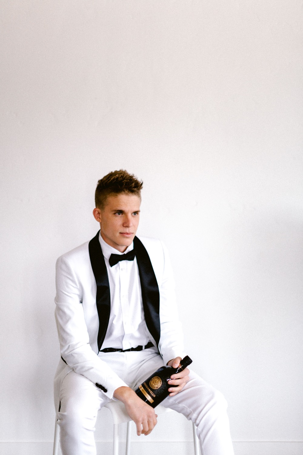 groom in white tux with black trim
