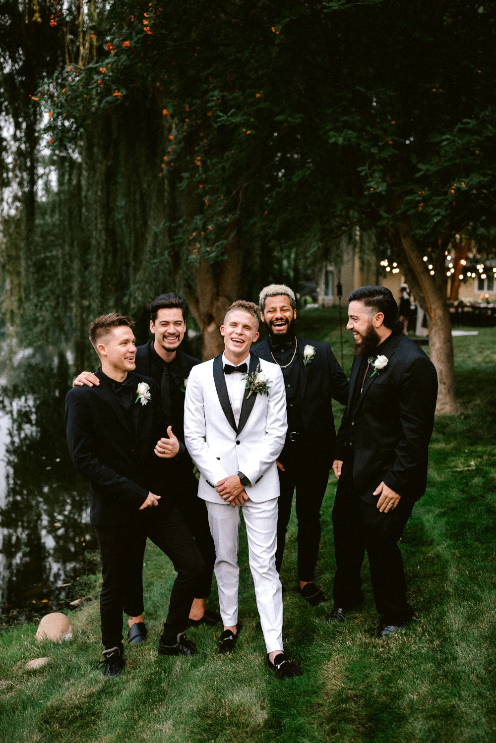 groomsmen in black and groom in white with black trim