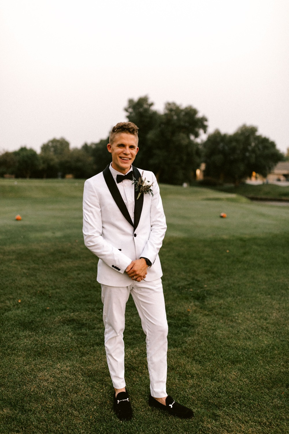 groom in all white tux with black trim