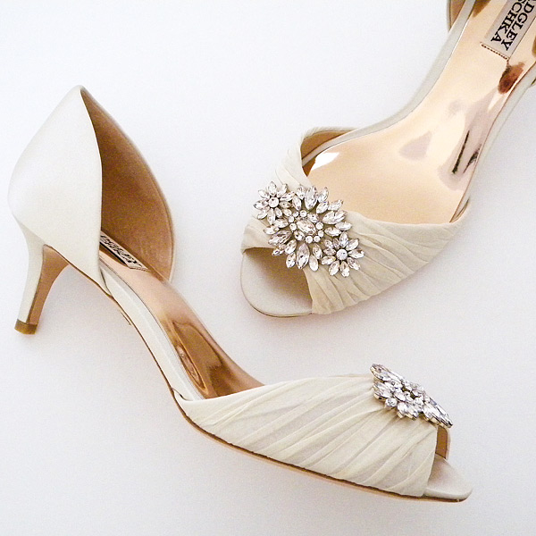 Gorgeous low heels that are long on glamour. D'Orsay style with pleated organza overlay at the toe, finished with a stunning rhinestone
